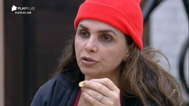 Luiza Ambiel comendo, com gorro na cabeça