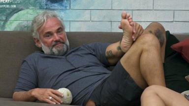 Mateus Carrieri relaxado no sofá, segurando uma bola em uma mão e o pé em outra