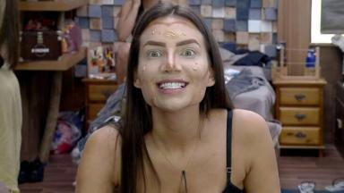Stéfani Bays de frente ao espelho, com rosto com maquiagem desforme, mostrando os dentes