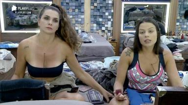 Luiza Ambiel e Victória Villarim se maquiando diante do espelho no quarto