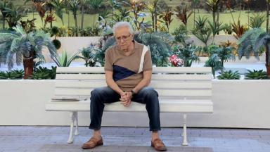 Carlos Alberto de Nóbrega sentado no banco de A Praça é Nossa