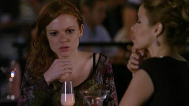 Cena de A Vida da Gente com Nanda sentada ao lado de Celina