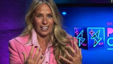 Adriane Galisteu gesticulando de blazer rosa em Power Couple