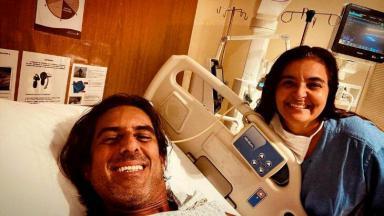 Adriano Melo sorridente com enfermeira em leito hospitalar