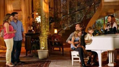 Ester e Cassiano veem Aberto sentado ao piano com os filhos no colo e Guiomar ao lado