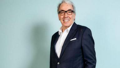 Alcides Nogueira posa para foto de pé e sorrindo
