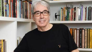 Alcides Nogueira posa para foto à frente de um armário de livros