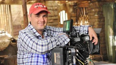Diretor Alexandre Avancini posa com as mãos apoiadas em câmera