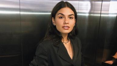 Allana Lopes de blazer preto no elevador