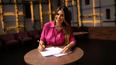Amanda Françozo assinando contrato