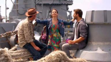 Cena de Flor do Caribe com Duque e Cassiano sentados no navio e Amaralina em pé