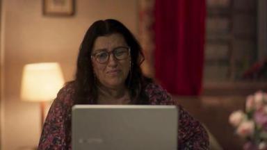 Lurdes chorando em frente ao computador em Amor de Mãe