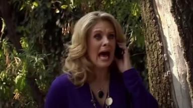 Cena de Amores Verdadeiros com Vitória gritando enquanto segura o telefone no ouvido