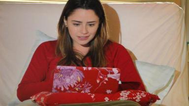 Ana sentada na cama com o laptop no colo