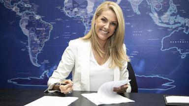 Ana Hickmann assinando contrato e sorrindo
