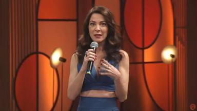 Ana Paula Padrão segurando microfone com mão direita e cara de espanto