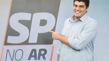 André Azeredo aponta para logo do SP no Ar