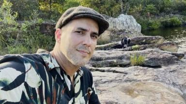 André Marques de boina com pedras e riacho ao fundo