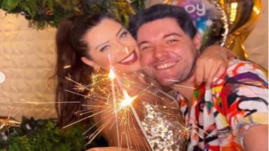 Andressa e Nasser estão abraçados e comemoram com uma vela na mão