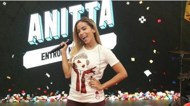 Anitta sorri com o microfone na mão