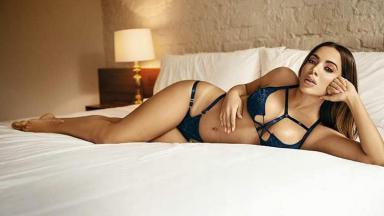 Anitta deitada em uma cama de lingerie