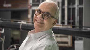 Arthur Xexéo, de lado, posa para foto, com óculos e sorrindo