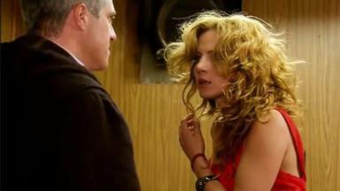 Augusto encara Renata que está com o cabelo desarrumado por causa do tapa que levou