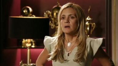 Adriana Esteves, como Carminha, de pé, com expressão séria e a boca aberta