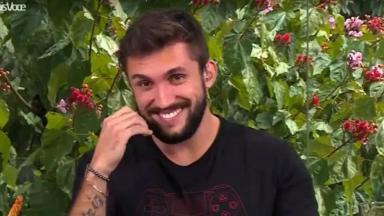 Arthur sorrindo com a mão na barba em entrevista à Ana Maria Braga