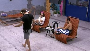 Caio está de pé andando pela área externa do BBB21 enquanto Fiuk e Gilberto estão sentados na cadeira