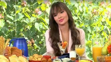 Thaís está sentada pensativa em frente a uma mesa de café de manhã