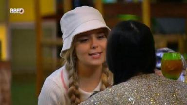 Viih tube está de chapéu branco e tranças no cabelo conversando com Juliette na festa do BBB21