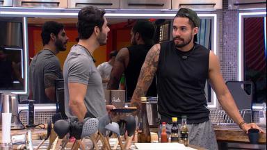 Rodolffo e Arcrebiano conversando na cozinha do BBB21