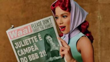 Anitta segura jornal com a manchete Juliette campeã