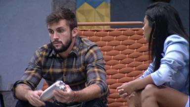 Arthur está com o olhar fixo no chão segurando uma garrafa ao lado de Pocah no BBB21