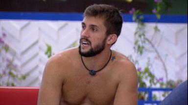 Arthur sem camisa está falando na área externa do BBB21