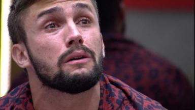 Arthur chorando olhando para frente na sala do BBB21