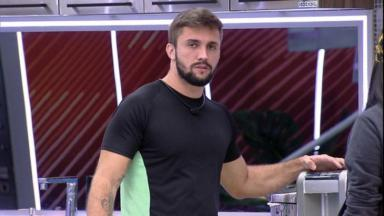 Arthur Picoli em pé na cozinha da xepa