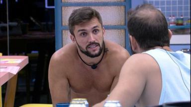 Caio e Arthur sentados durantes conversa na cozinha do BBB21