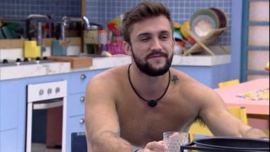 Arthur está sem camisa sorrindo com um copo na mão sentado na cozinha do BBB21