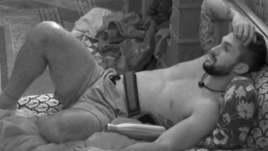 Arthur no escuro está deitado na cama do BBB com a mão no cabelo