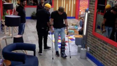 Caio Afiune andando de muleta no BBB21