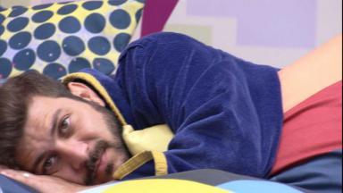 Caio está deitando de lado com a mão debaixo do rosto e roupão do líder no sofá da sala do BBB21