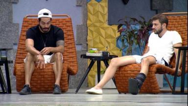 Caio e Rodolffo sentados conversando na área externa do BBB21