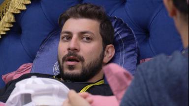 Caio está deitado no quarto do líder conversando com Gilberto no BBB21