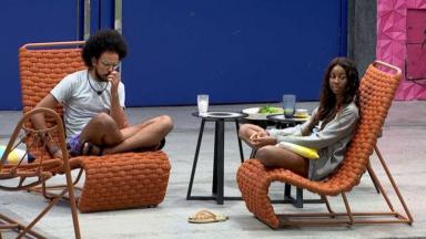 João Luiz e Camilla de Lucas sentados na área externa do BBB21