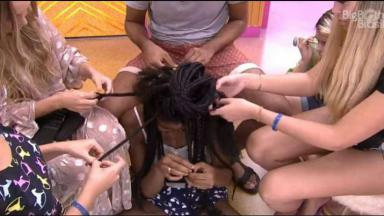 Camilla está sentada no chão com os brothers em volta retirando as tranças dela