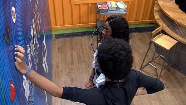 Camilla de Lucas e João Luiz desenhando mexendo no painel da academia do BBB21