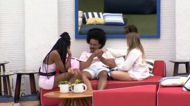 Camilla de Lucas, João Luiz e Carla Diaz sentados conversando na área externa do BBB21