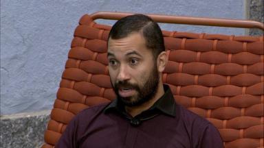 Gilberto sentado na área externa do BBB21